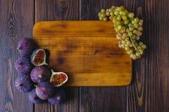 Drewniana kuchni deska z fig winogronami na nim i owoc Fotografia Stock