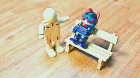 Drewniana lala która pozuje zagrożenie robota obsiadanie na ławce zdjęcia stock