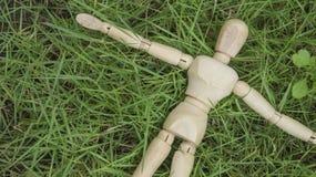 Drewniana ludzka postać kłaść puszek na trawa ogródzie relaksuje Obrazy Royalty Free