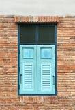 Drewniana nadokienna żaluzja cyan w tradycyjnej brickwork powierzchowności w zdjęcie stock