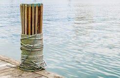 Drewniana nautyczna listwa z arkaną zawijającą wokoło go przy nabrzeżem obrazy stock