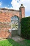 Drewniana ogrodowa brama z czerwonym ściana z cegieł Fotografia Royalty Free