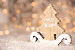 Drewniana ornament wycinanka w formie sosny z tekstów Wesoło bożymi narodzeniami i bokeh żółci bożonarodzeniowe światła z kopii p obraz royalty free