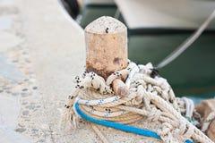 Drewniana poczta z cumowniczymi arkanami dla wiązać łodzie i statki Zdjęcia Stock