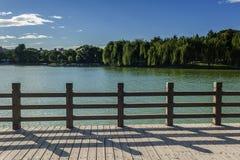 Drewniana poręczówka przy brzeg jeziora w parku Fotografia Royalty Free