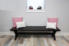 drewniana posadzkowa drewniana ławka i poduszki na nim blisko okno fotografia royalty free