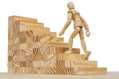 Drewniana postać biega w górę wysokich schodków jako metafora dla pracy i kariery zdjęcia royalty free