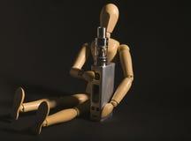 Drewniana postać trzyma elektronicznego papieros Obraz Royalty Free