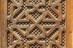 Drewniana praca w kwadratowym wzorze na drzwiach madarsa w Fes, Maroko Zdjęcia Stock