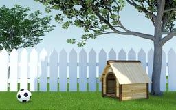 Drewniana psia psiarnia pod drzewnym cieniem na zielonej trawy łące z piłki nożnej piłki i białego drewnianym ogrodzeniem Zdjęcie Royalty Free