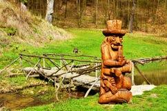 Drewniana rzeźba waterman przy drewnianym mostem przy rzeką Obrazy Stock