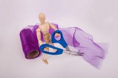 Drewniana spajająca manikin lali mienia nożyc tkaniny purpurowa tiulowa rolka w tle zdjęcia stock