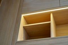 Drewniana spiżarnia z kreślarzami, opróżnia półki i PROWADZĄCYCH światła współczesne meble obraz royalty free