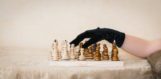 drewniana szachowa deska z postaciami i ludzką ręką w czarnej rękawiczce Zdjęcia Stock