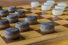 Drewniana szachownica z warcabami interliniującymi na stołowym zbliżeniu zdjęcie royalty free