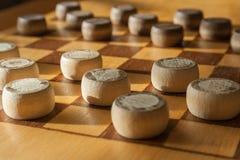 Drewniana szachownica z warcabami interliniującymi na stołowym zbliżeniu obraz stock