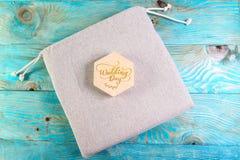 Drewniana szkatuła z inskrypcją na dzień ślubu na bieliźnianej torbie na błękitnym drewnianym tle obraz stock
