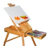 Drewniana sztaluga i jesień liście na pustej kanwie Fotografia Stock