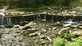 Drewniana tama na małej halnej rzece i stos kamienie zbiory wideo
