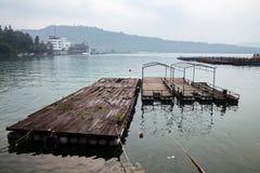 Drewniana tratwa i łodzie w jeziorze obraz stock