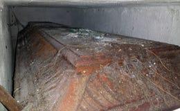 drewniana trumna z religijnym krzyżem up w grzebalnej recesi okrywającej w pajęczynach Zdjęcia Stock