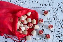 Drewniane baryłki dla bingo w czerwonej torbie przeciw tłu karty zdjęcie stock