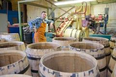 Drewniane baryłki produkcja bednarza używa młot i narzędzia w warsztacie obraz royalty free