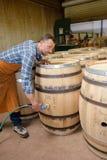 Drewniane baryłki produkcja bednarza używa młot i narzędzia w warsztacie fotografia royalty free