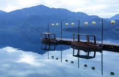 Drewniane łodzie przy molem z spokojnym jeziorem Obraz Stock