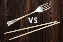 Drewniane pary chopsticks vs rozwidlenie Abstrakcjonistyczny konceptualny wizerunek Zdjęcie Stock