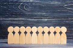 Drewniane postacie ludzie stoją z rzędu w formaci na tle heban Pojęcie dyscyplina rewizja dla puszki obraz stock