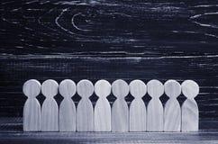 Drewniane postacie ludzie stoją z rzędu w formaci na tle heban Pojęcie dyscyplina rewizja dla puszki obraz royalty free