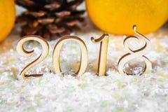 Drewniane postacie 2018 na śniegu Bożenarodzeniowa atmosfera nowy rok 2018 Mandaryny i rożki Zdjęcie Royalty Free