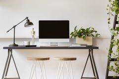 Drewniane stolec przy biurkiem z lampą, komputerem stacjonarnym i rośliną w białym workspace wnętrzu, Istna fotografia fotografia royalty free