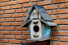 Drewnianego domu ptak, stary dom dla ptaka na czerwonym ściana z cegieł, mały drewniany dom na ścienny starym fotografia stock