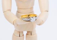 Drewnianego kukiełkowego mienia złoty pierścionek z diamentem. Obrazy Stock