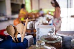Drewnianego naczynia kuchenny artykuły dekoruje z rozmytymi ludźmi w tle Zdjęcia Royalty Free