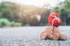 Drewnianego samochód zabawki przewożenia czerwony serce na wierzchołku Zdjęcia Royalty Free