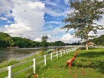 Drewnianej ławki park blisko rzeki publicznie, fotografia stock