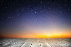 Drewnianej deski i gwiaździstej nocy tło w wschodu słońca czasie obrazy stock