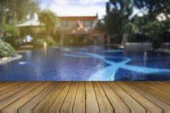 Drewnianej deski pusty stół przeciw zamazanemu pływackiego basenu tłu Perspektywiczny brown drewno nad pływackim basenem zdjęcia stock