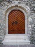 Drewniani łękowaci drzwi przy średniowiecznym kasztelem w Budva Obrazy Royalty Free