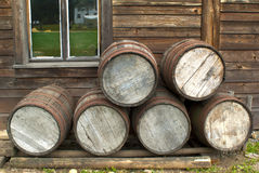Drewniani barrells wypiętrzali up przed Pionierską drewnianą beli kabiną XIX Zdjęcia Royalty Free