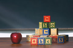 Drewniani bloki i jabłko na biurku Zdjęcia Stock