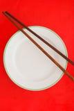 Drewniani chopsticks na czerwonym tle obrazy stock