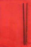 Drewniani ciemni chopsticks na czerwieni zdjęcia stock