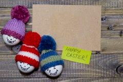 drewniani Easter jajka Emoticons w trykotowym kapeluszu z pom-poms han Zdjęcie Stock