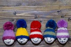 drewniani Easter jajka Emoticons w trykotowym kapeluszu z pom-poms han Obraz Stock