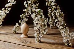 Drewniani Easter jajka w?r?d kwiatono?nej wi?ni rozga??ziaj? si? na wie?niaka stole symboliczny sk?ad wiosna wakacje dla prezent  obrazy stock