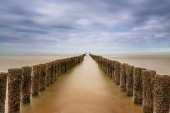 Drewniani fens które biegają w morze z niebieskim niebem zdjęcia stock